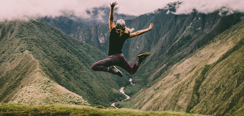 A woman exercising on top of a mountain